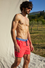 Man wearing a Plain Coral swimsuit with elasticated belt