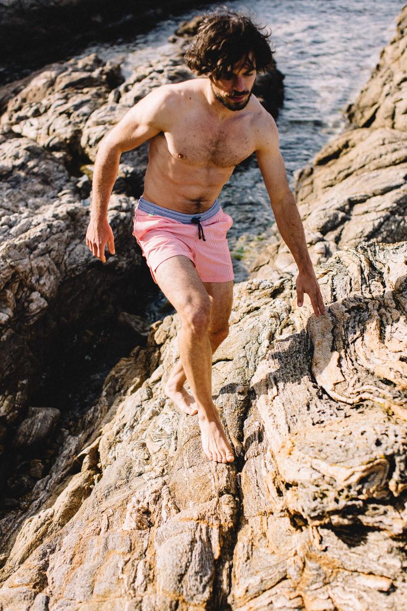 Man wearing a Coral Seersucker swimsuit with elasticated belt