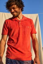 man wearing a terracotta terry cloth polo