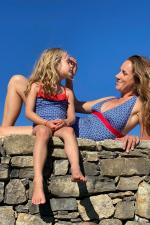 mother and daughter wearing a matching navy kangaroos swimsuit
