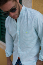 man wearing a green striped mandarin collar shirt